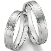 Schlichte Eheringe aus Silber mit einem Brillant