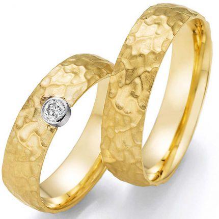 Hochzeitsringe aus Gelbgold mit Hammerschlag-Oberfläche und besonders gesetztem Brillant